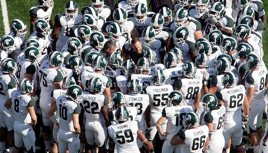 Michigan State head coach Mark Dantonio, center, speaks to his team inside a huddle on the Michigan Stadium field before an NCAA college football game with Michigan, Saturday, Oct. 9, 2010, in Ann Arbor, Mich. Dantonio is coaching the game from the press box. (AP Photo/Tony Ding)