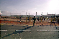 An Israeli soldier gestures next to a closed gate to Palestinian farmers as they wait to make their way to their lands on the other side of the new separating fence in the Palestinian town of Jbareh to harvest the olive trees, October 28, 2004. According to Israeli army the gate was closed for the last ten days due to security reasons. Palestinian farmers have difficulties to harvest their olive trees due the new security conditions. Photo by Quique Kierszenbaum