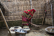 25 year old Sri Kanthi Devi carries on with her daily chores, here she sweeps the courtyard of their house in Ramgarwa village in Raxaul district in Bihar, India.