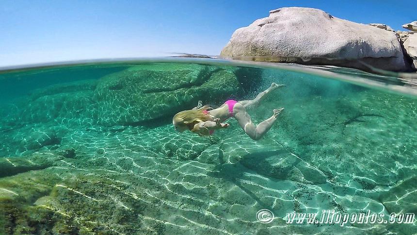 Υoung woman swims at the bottom of an exotic beach on half underwater view
