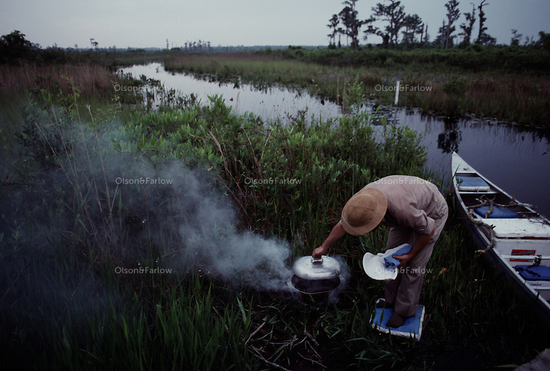 """A camper checks the fire as he cooks for the evening meal on a three day wilderness canoe trip through the Okefenokee Swamp. <br /> <br /> Okefenokee means """"Land of the Trembling Earth"""" in a Native American language. The term refers to the natural processes as peat bubbles up from the bottom of the swamp, vegetation attaches itself, and plants begin growing to form little islands. The effect of walking on this unstable land as been described as being able to dance with a tree of similar weight."""