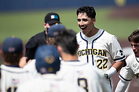 Michigan Wolverines outfielder Tito Flores (22) is greeted by his teammates after hitting a home run against the Maryland Terrapins on May 23, 2021 in NCAA baseball action at Ray Fisher Stadium in Ann Arbor, Michigan. Maryland beat the Wolverines 7-3. (Andrew Woolley/Four Seam Images)