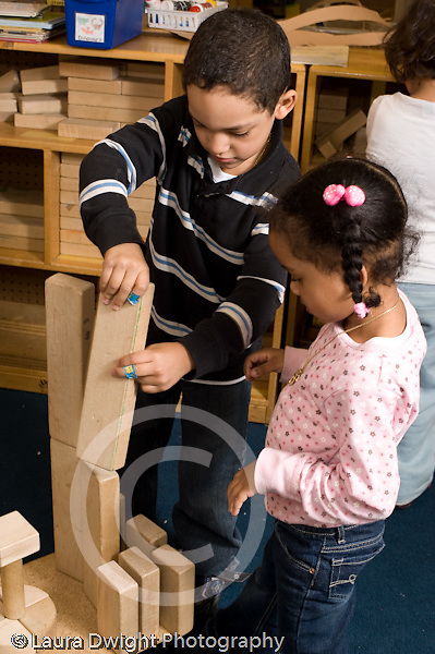 Preschool 4-5 year olds block area children playing with wooden blocks boy and girl working together girl watching boy set block in place vertical
