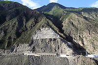 The side of a mountain has been cut away to allow for the building of a road that leads to the Maoergai Dam. Large-scale damming projects have caused knock-on environmental effects that have altered the local landscape forever. South-east Tibetan Plateau, in Sichuan Province, western China.