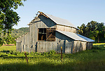 Wooden barn with corrugated siding and roof, spring