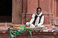 Fatehpur Sikri, Uttar Pradesh, India.  Fabric Vendor.  Visitors to the tomb of Sheikh Salim Chishti leave offerings of fabric on his grave.