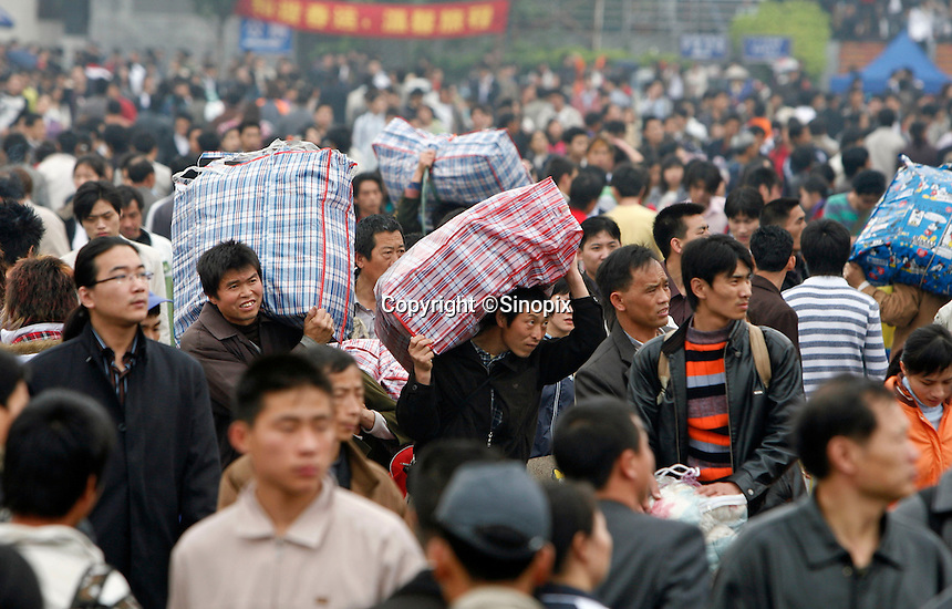 Migrant workers with loads of baggages walking towards the entrance of the train station in Guangzhou, China..16 Feb 2007