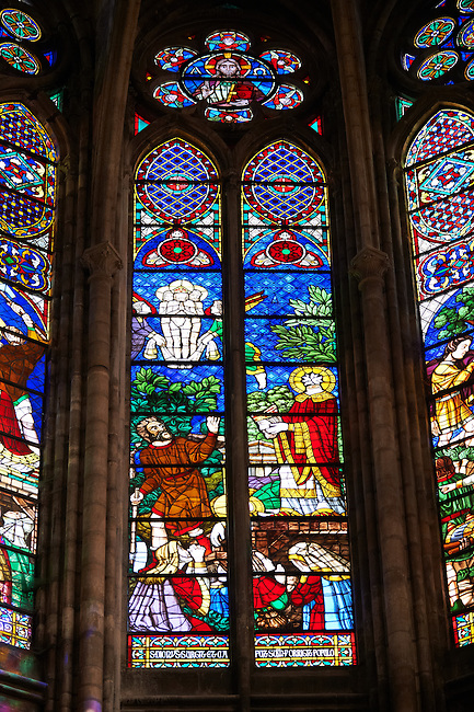 Medieval Gothic stained glass window showing  scenes from the Martyrdom of Saint Denis. In this scene he miraculously walks after is beheading. The Gothic Cathedral Basilica of Saint Denis ( Basilique Saint-Denis ) Paris, France. A UNESCO World Heritage Site.