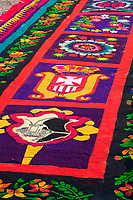Antigua, Guatemala. Detail of an alfombra (carpet) of colored sawdust, pine needles, and other traditional materials decorating the street in front of the Ayuntamiento (town hall, or Casa del Cabildo) in advance of the passage of a procession on Good Friday morning, La Semana Santa.  The alfombra will be finished only a couple of hours before the passage of the procession, after which the remains will be quickly swept away by municipal street sweepers.