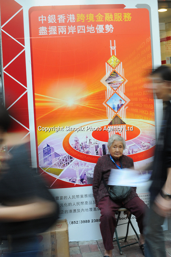 An old woman sits in front of an advert of a bank at the Hong Kong Stock Exchange in Hong Kong.................
