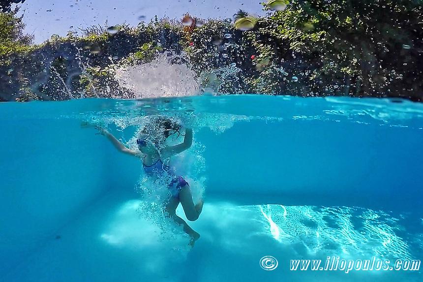 Υoung girl swims at the pool on half underwater view
