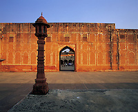 Courtyard with stone lantern and arched doorway in evening light, Amber Fort, Jaipur, Indi
