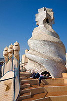 Spain, Catalonia, Barcelona, Casa Mila, La Pedrera, Barcelona district, A couple relaxing beneath one of the sculptures on the roof of Casa Mila, This is the most avant-garde  of all the works  of Antonii Gaudi