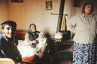 Bulgaria. Province Oblast Lovech. Lukowit. Gypsy family at home. A grandmother, seated on a bed, holds her granddaughter in her arms and on her knees. Her son and his wife are also in the room. Romany culture. Three generations. © 1997 Didier Ruef
