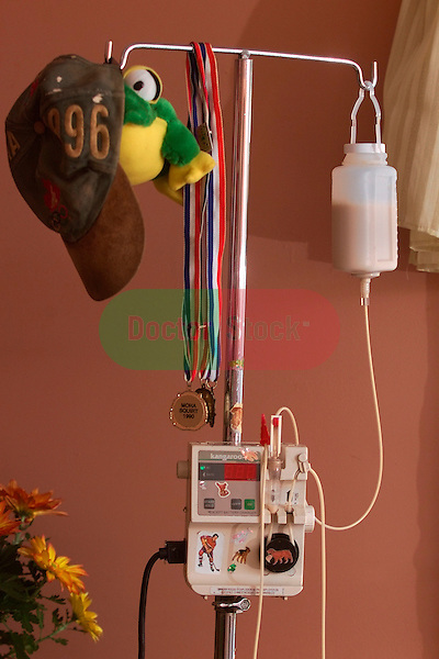 bottle of liquid medication and pump hanging on stainless steel stand in hospital room with young man's personal belongings, hat, sports medals, symbols of youth