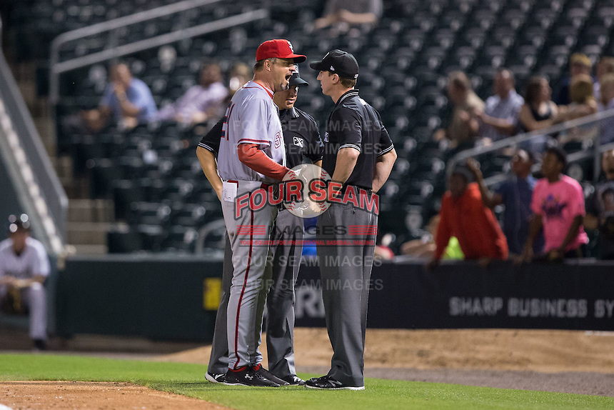 Syracuse Chiefs manager Billy Gardner Jr. (24) argues a call with first base umpire Alex Tosi as third base umpire Chris Segal looks on during the game against the Charlotte Knights at BB&T BallPark on June 1, 2016 in Charlotte, North Carolina.  The Knights defeated the Chiefs 5-3.  (Brian Westerholt/Four Seam Images)