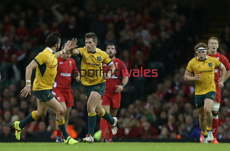 Outside half Bernard Foley celebrates with Adam Ashley-Cooper after kicking a late drop goal to give Australia the lead.<br /> Dove Men Series 2014<br /> Wales v Australia<br /> Millennium Stadium<br /> 08.11.14<br /> ©Steve Pope-SPORTINGWALES