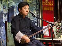 """Suzhou, Jiangsu, China.  Young Man Playing a """"Three Strings."""""""