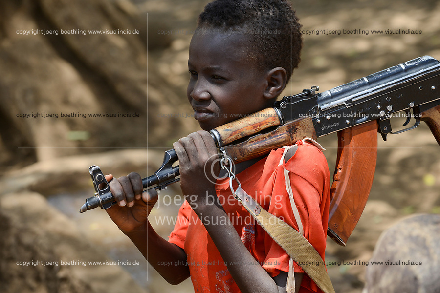 ETHIOPIA, Southern Nations, Lower Omo valley, Kangaten, village Kakuta, Nyangatom tribe, boy with machine gun Kalashnikov AK-47 for protection from cattle raids by hostile neighbor Turkana warriors, the gun is marked with SSPSHQ South Sudan Police Headquarter  / AETHIOPIEN, Omo Tal, Kangaten, Dorf Kakuta, Nyangatom Hirtenvolk, Junge Losikiria traegt Maschinengewehr Kalaschnikow AK-47 zum Schutz vor Ueberfaellen durch Turkana Krieger, Gewehr hat Markierung SSPSHQ des Sued Sudan