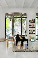 A modern white living room with a tiled floor and barrel ceiling. A black sofa stands on a rug back to back with two wooden armchairs. A full height glass door gives access to a garden.