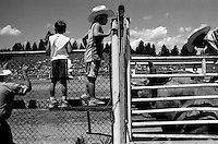 A boy looks on as a cowboy gets ready for the bullriding competition at the annual Lincoln Rodeo in Lincoln, MT in June 2006.  The Lincoln Rodeo is an open rodeo, which means competitors need not be a member of a professional rodeo association.