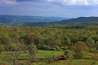 Peaceful valley scene in Spruce Knob West Virginia.  The valley is surrounded with mountains and a fence, barn and shed are visible in the valley