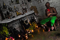 A Cuban man, the Palo religion priest, sits in his home temple and prepares himself for a ritual, Santiago de Cuba, Cuba, August 1, 2009. The Palo religion (Las Reglas de Congo) belongs to the group of syncretic religions which developed in Cuba amongst the black slaves, originally brought from Congo during the colonial period. Palo, having its roots in spiritual concepts of the indigenous people in Africa, worships the spirits and natural powers but can often give them faces and names known from the Christian dogma. Although there have been strong religious restrictions during the decades of the Cuban Revolution, the majority of Cubans still consult their problems with practitioners of some Afro Cuban religion.