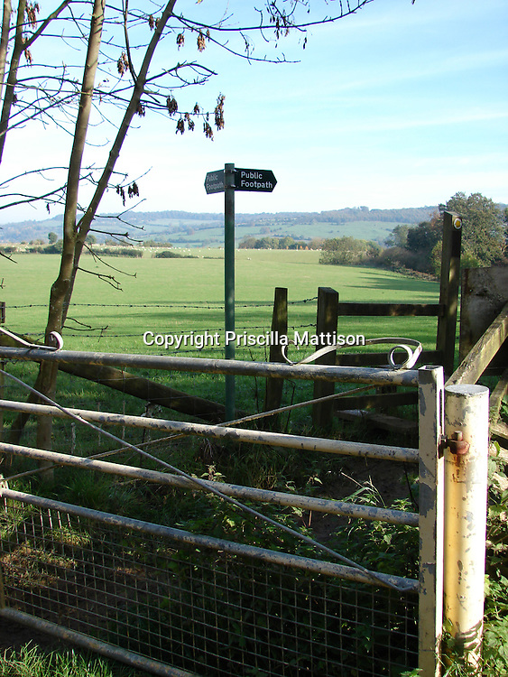 """Cotswolds, England - November 5, 2006:  A """"public footpath"""" sign stands near a gate and wooden stile along the Cotswold Way."""