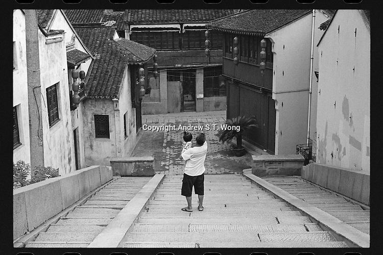 A local resident talks to a little girl as he walks across   Qingming Bridge over the ancient Beijing-Hangzhou Grand Canal in Wuxi, Jiangsu province, China, August 2013.