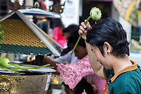 Bangkok, Thailand.  Worshiper Sprinkling Holy water on her Head with a Lotus Blossom, Royal Grand Palace Compound.