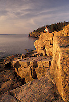 AJ4476, Acadia, Acadia National Park, Maine, Atlantic Ocean, A woman sits on the rocky coastline looking out at the ocean in the early morning light in Acadia Nat'l Park in the state of Maine.