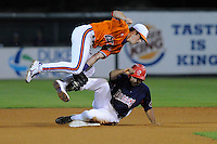 Shortstop Steve Wilkerson (17) of the Clemson Tigers tumbles over the bag as he tags out Osvaldo Avila (40) of College Lafleche of Canada attempting to steal second base in the sixth inning of a fall scrimmage on October 17, 2013, at Fluor Field at the West End in Greenville, South Carolina.