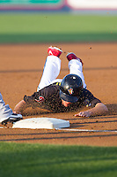 Brock Stassi (28) of the Reading Fightin Phils slides head first into third base against the Akron Rubber Ducks at FirstEnergy Stadium on June 19, 2014 in Wappingers Falls, New York.  The Rubber Ducks defeated the Fightin Phils 3-2.  (Brian Westerholt/Four Seam Images)