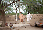 25 JULY 2011: Basti Mahraan Village, Punjab, Pakistan.    Mahar Abdul Latif (R), a former member of Muslim terrorist group Lashkar-i-Taiba (LeT) at his home village of Basti Mahraan in Pakistan with fellow villager Bachu Ram, a Hindu. After Ram offered to donate his rare blood type to save the life of a muslim woman, relations thawed in the traditional violence between the Muslims and Hindu's of the village. Picture by Graham Crouch/Toronto Star