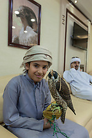 "United Arab Emirates (UAE). Abu Dhabi Falcon Hospital. <br /> A young boy with his father speaking on the phone are seated in the waiting room of the falcon's hospital. The smiling kid holds on a glove a falcon with a hood. The hospital is considered the leading center in the world for falcon medical care. It is equipped with everything a hospital requires for treating humans, except that the patients have wings. Both men wear the traditional thobes. A thawb (thobe, dishdasha, kandora) is an ankle-length garment, usually with long sleeves, similar to a robe, kaftan or tunic, commonly worn in the Arabian Peninsula. The headdress is called ghutrah. Falcons are birds of prey in the genus Falco, which includes about 40 species. Adult falcons have thin, tapered wings, which enable them to fly at high speed and change direction rapidly. Additionally, they have keen eyesight for detecting food at a distance or during flight, strong feet equipped with talons for grasping or killing prey, and powerful, curved beaks for tearing flesh. Falcons kill with their beaks, using a ""tooth"" on the side of their beaks. The United Arab Emirates (UAE) is a country in Western Asia at the northeast end of the Arabian Peninsula. 19.02.2020  © 2020 Didier Ruef"