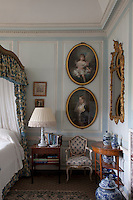 Two 19th century portraits of children hang in a corner of the Dutchess of Beaufort's pale blue and white bedroom