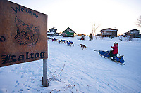 Sebastian Schnuelle runs up the bank from the Yukon River and into the Kaltag checkpoint during the 2010 Iditarod