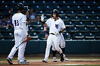 Jose Rodriguez (24) of the Winston-Salem Dash is greeted at home plate by his teammates after hitting a grand slam against the Greensboro Grasshoppers at Truist Stadium on August 11, 2021 in Winston-Salem, North Carolina. (Brian Westerholt/Four Seam Images)