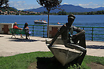 Couple and boaters along Lake Maggiore in Arona, lake district in northern Italy.