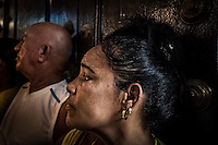 Havana, Cuba, sept 2014.A woman in Church during  the day of the Virgin of Charity of Copper.                            In recent years, Raul Castro has made several economic measures for the people of the island. Cubans can now buy and sell apartments or cars, can stay in hotels on the island and can travel abroad with minor difficulties. Most of the global economists believe that these changes are moving in the right direction but its positive effects on people are very slow. Cubans continue to struggle daily through the streets of Havana with humor and zest for life.                                  En los ultimos años Raul Castro ha realizado varias medidas economicas para el pueblo de la isla. Ahora los cubanos pueden comprar y vender departamentos o coches, pueden alojarse en hoteles de la isla y pueden viajar al extranjero con menores dificultades. La mayor parte de los economistas mundiales consideren que estos cambios se mueven en la justa direccion pero sus efectos positivos sobre la gente son muy lentos. Los cubanos siguen luchando a diario por las calles de La Habana con humorismo y ganas de vivir.