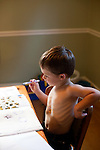 My older son, then four years old, decorates his sticker book and himself.