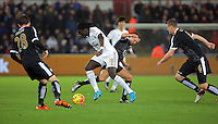 Bafetimbi Gomis of Swansea is challenged by Danny Drinkwater of Leicester City (C) during the Barclays Premier League match between Swansea City and Leicester City at the Liberty Stadium, Swansea on December 05 2015
