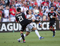 Daniel Woolard (21) of D.C. United fights for the ball with Camilo Sanvezzo (7) of the Vancouver Whitecaps during a Major League Soccer match at RFK Stadium in Washington, DC. D.C. United lost to the Vancouver Whitecaps, 1-0.