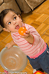 10 month old baby girl standing or walking  holding toy ball container vertical