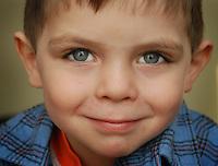 boy wearing flannel smiles