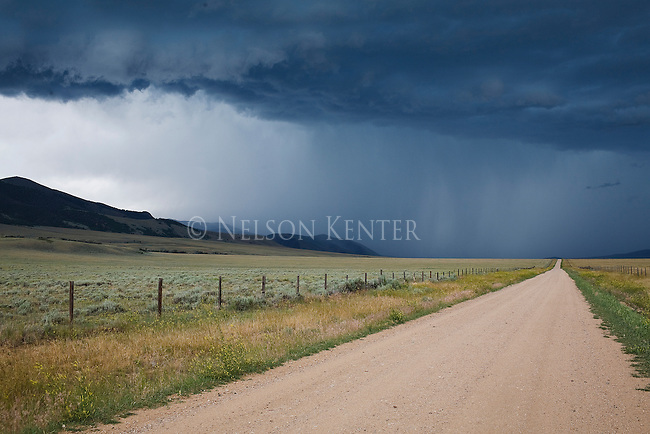 Storm clouds bringing summer rain and a rural gravel road near Dillon, Montana