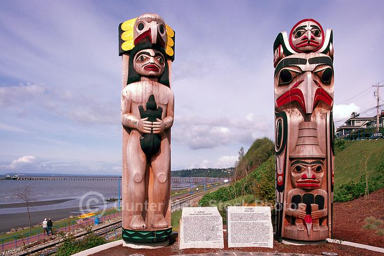 White Rock, BC, British Columbia, Canada - Totem Poles in Lions Park along Seaside Promenade Walkway and Semiahmoo Bay - Coast Salish Totem Pole (left) and Haida Totem Pole (right)