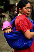 Cusco, Peru. Woman in red dress with baby in a pink hat in a blue cloth on her back.