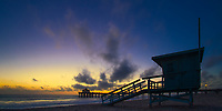 Colorful sunset on famous Manhattan Beach lifeguard tower, with the pier and Roundhouse Aquarium silhouettes in the background, Los Angeles California