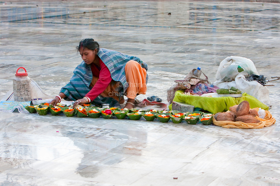 India, Rishikesh.  Woman Preparing Leaf-baskets of Marigold and Rose Offerings to Sell to Early-morning Worshippers at the River Ganges (Ganga).